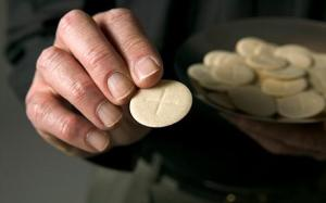 Priest holding out communion wafer